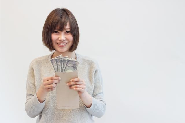 お金をもって微笑む若い日本人女性