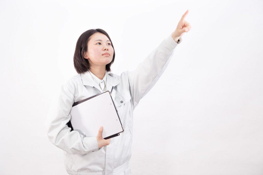 作業着を着て遠くを指さす女性作業員