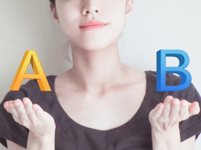 右手に「A」、左手に「B」を持つ女性