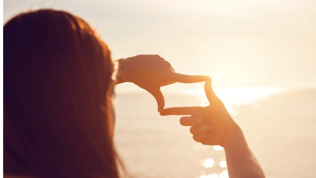 朝日の写真を撮る女性