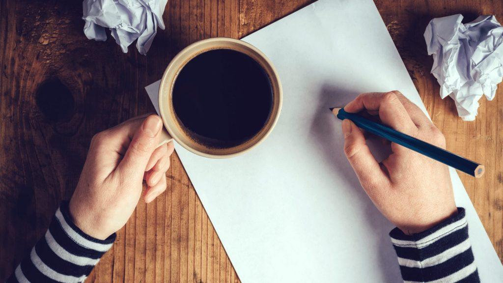 コーヒーを飲みながら記事を書く女性ライター