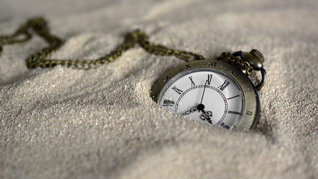 砂の中に埋もれているアンティークな懐中時計