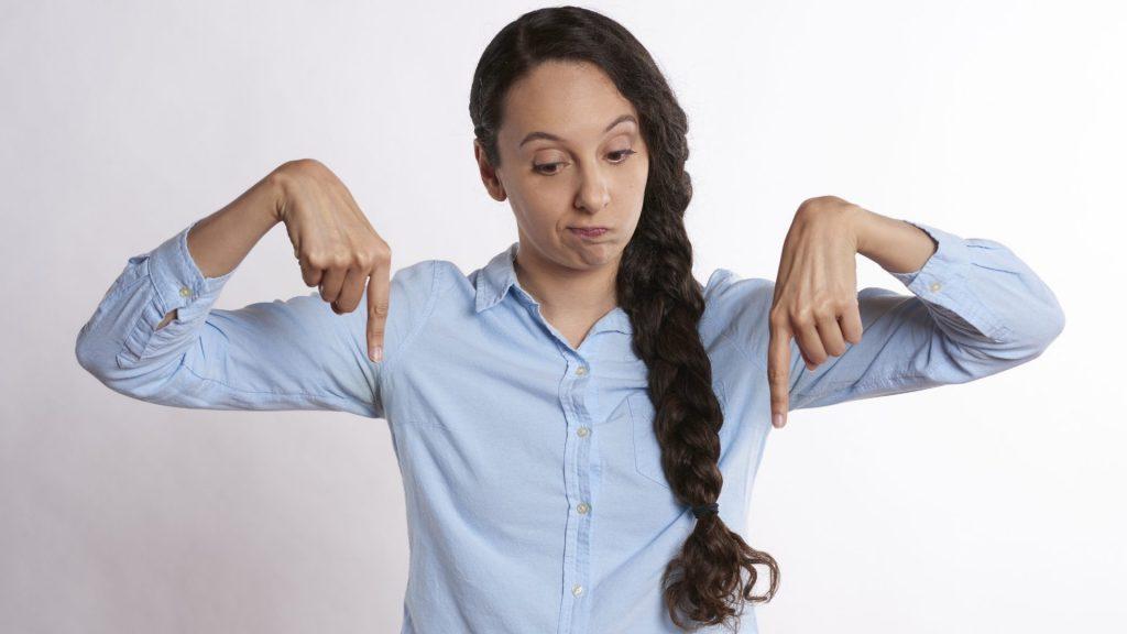 両指で指で下を指している女性