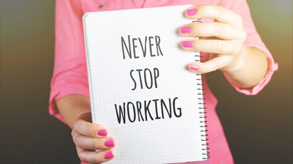 「never stop working」と書かれたノートを持つ女性