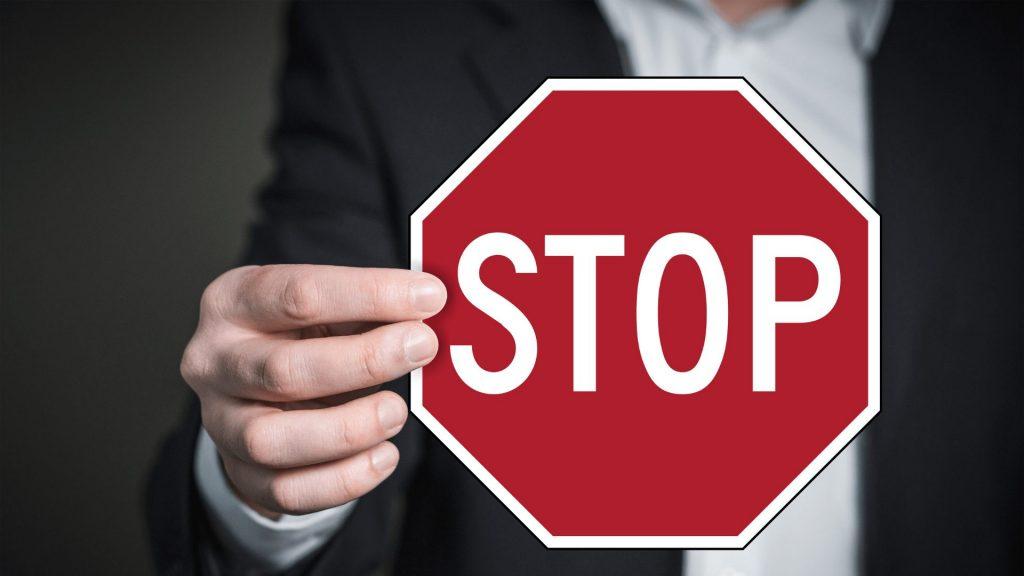 「stop」とと書かれたステッカを持つ女性